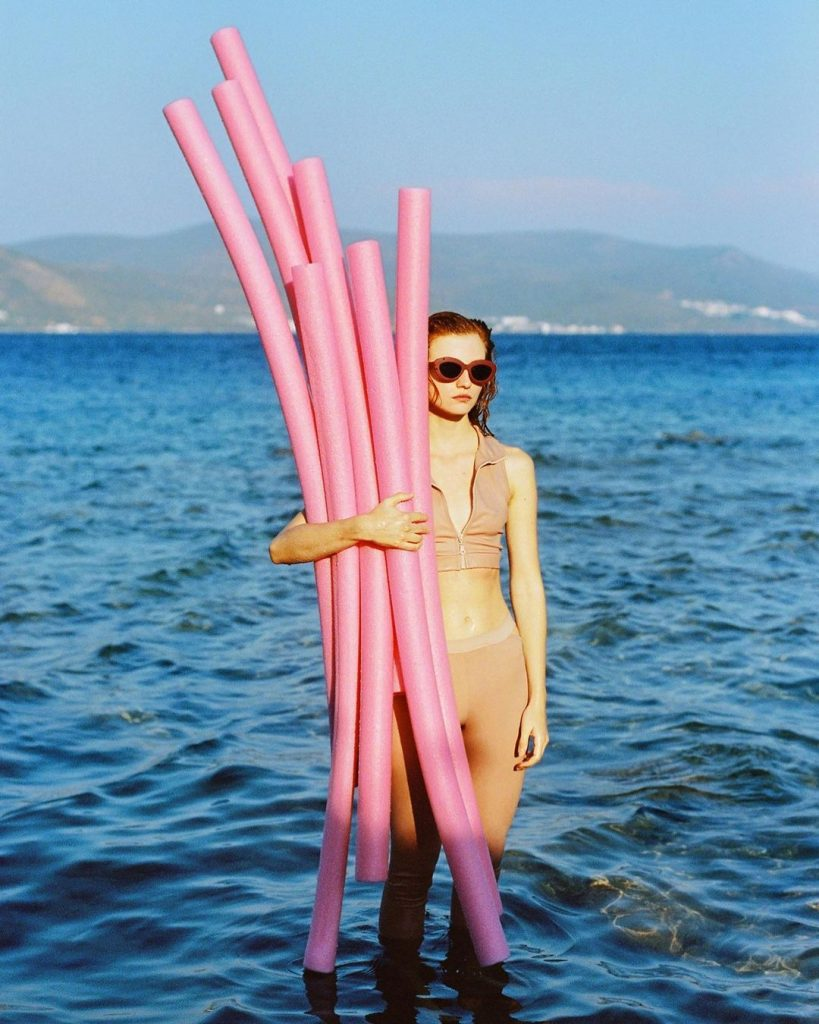 Woman holding pink plastic tubes in the ocean.